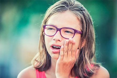 Почему болят зубы после установки брекетов